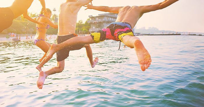 Kids jumping off the back of a bentley pontoon.